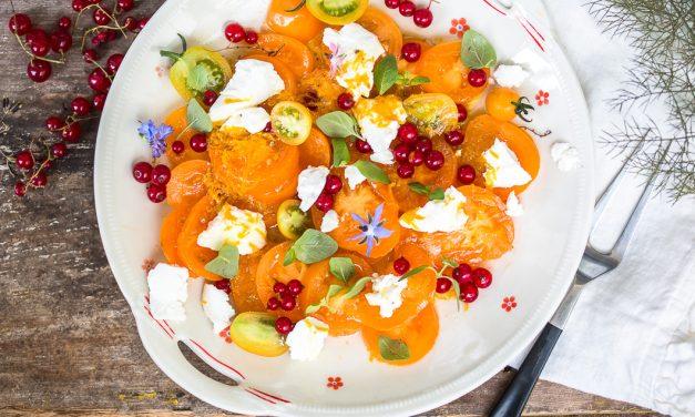 Salat mit gelben Tomaten, roten Johannisbeeren, Ziegenfrischkäse und Orangenvinaigrette